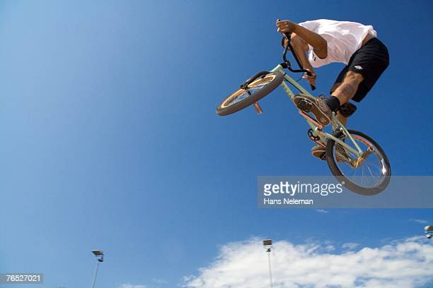 Young man with bicycle, low angle view