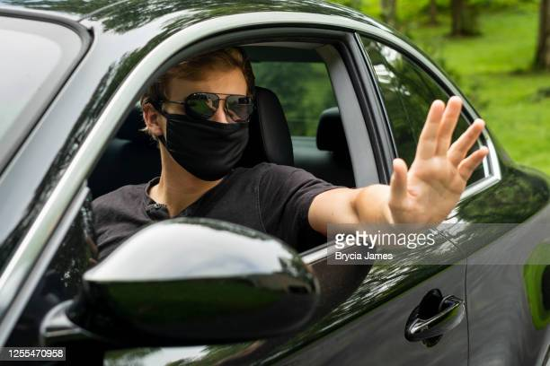 young man with black covid-19 mask, sunglasses driving car - brycia james stock pictures, royalty-free photos & images