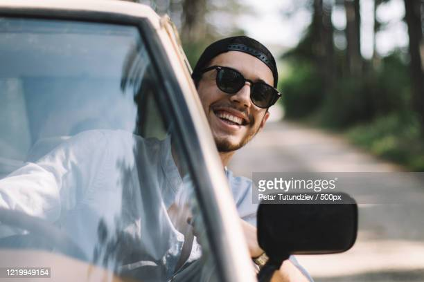 young man with black hair and sunglasses looking through window of car while driving and smiling at camera - サングラス ストックフォトと画像