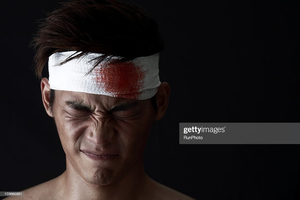 young man with bloody bandage on forehead : Stock Photo