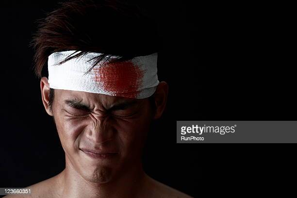 young man with bloody bandage on forehead