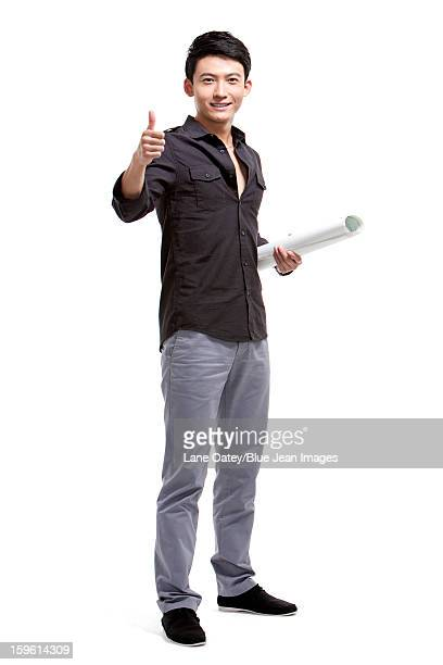 Young man with blueprint doing thumbs up