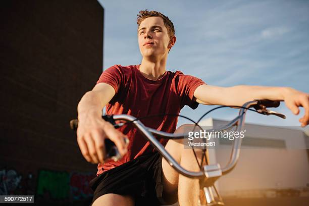 young man with bmx bicycle looking away - bmx cycling stock pictures, royalty-free photos & images