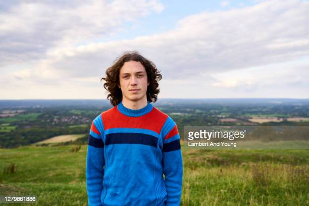 young man with bright sweater looking serious in the outdoors - young men stock pictures, royalty-free photos & images