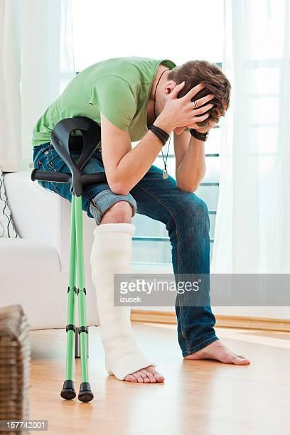 Jeune homme avec une jambe cassée à la