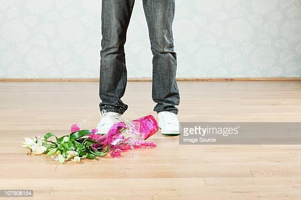Junger Mann mit gebrochenen vase Blumen auf der Etage