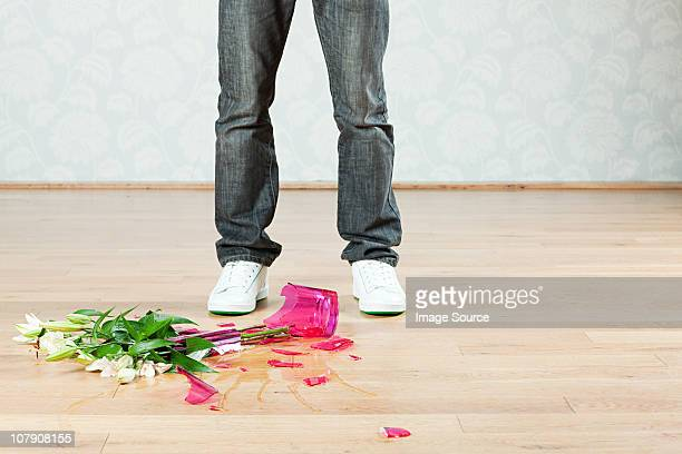 Young man with broken vase of flowers on floor
