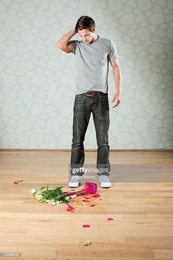 Young Man With Broken Vase Of Flowers On Floor High-Res ...