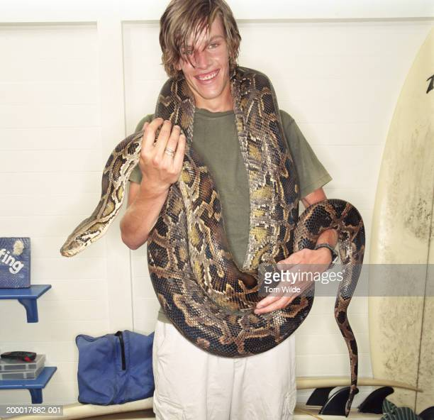 Young man with burmese python (Python molurus bivittatus) on shoulders