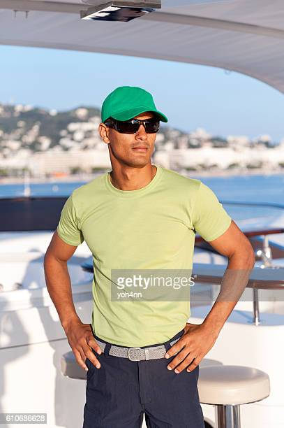 Young man with cap standing on yacht