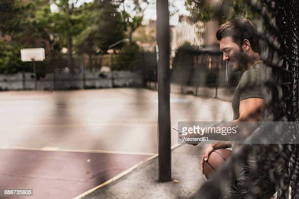 Young man with cell phone and basketball on an outdoor court