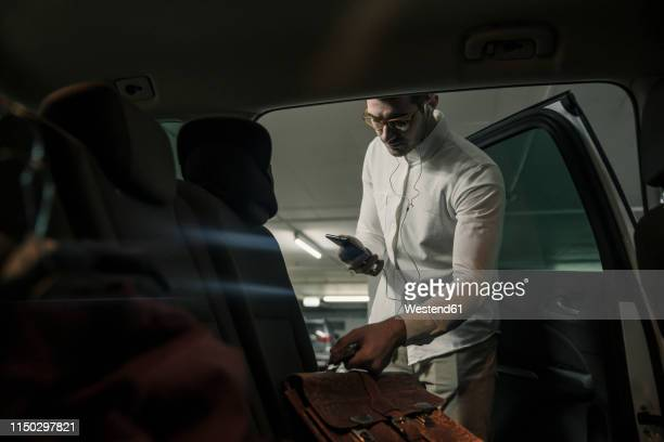 young man with cell phone and earphones taking bag out of car - disembarking stock pictures, royalty-free photos & images