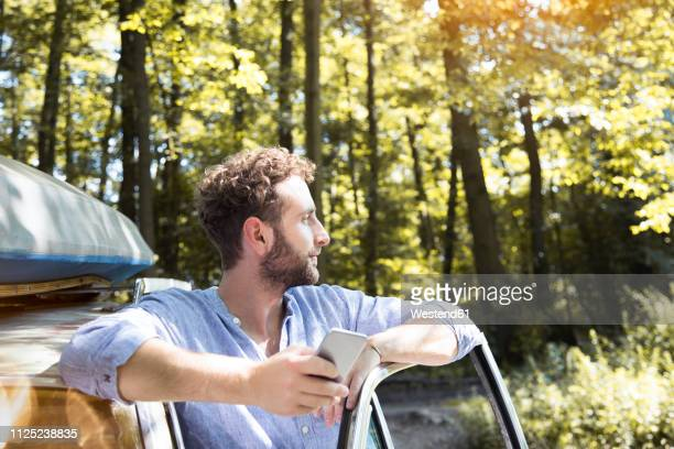 young man with cell phone at car in forest - wochenendaktivität stock-fotos und bilder
