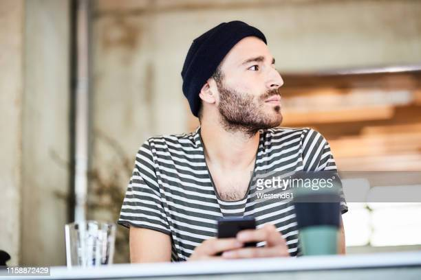 young man with cell phone wearing a beanie looking around - waiting stock-fotos und bilder