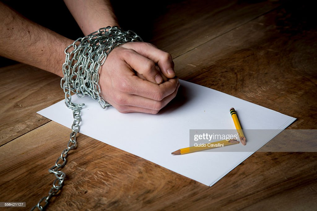 Young man with chains wrapped around his wrists, paper and broken pencil in front of him, focus on hands : Stock Photo