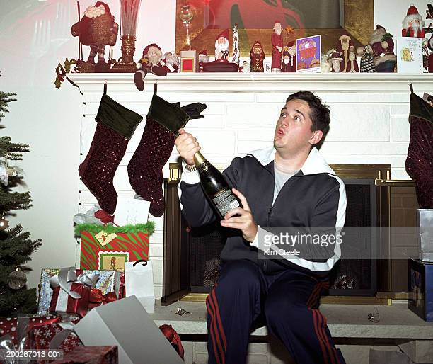 Young man with champagne bottle looking up at Christmas celebration