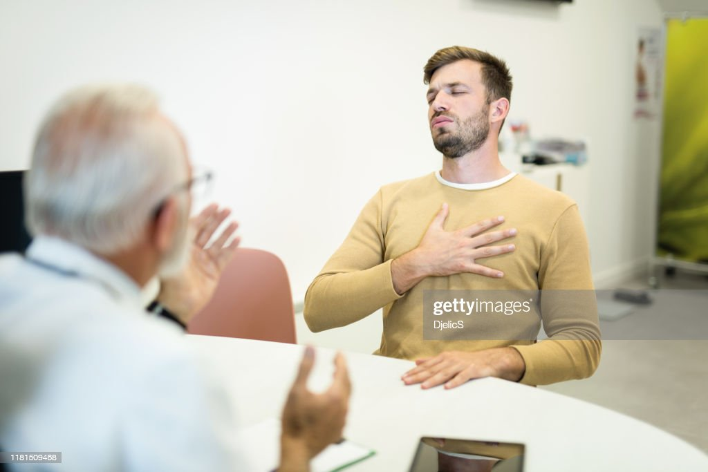 Young man with chest pain and breathing problems visiting a doctor. : Stock Photo