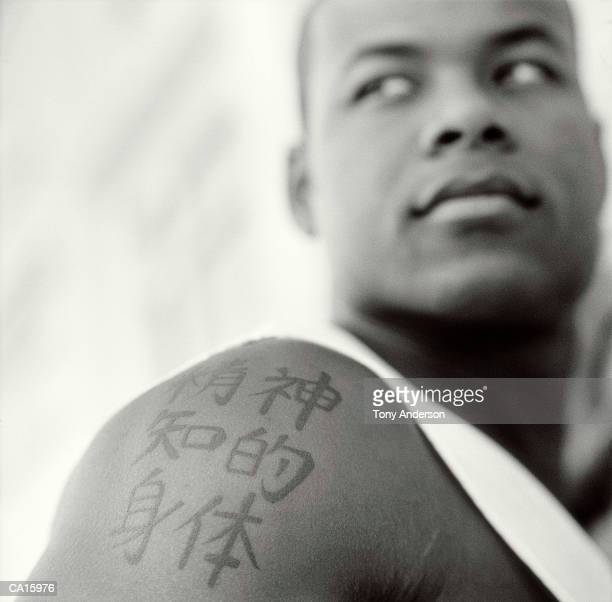 Young man with chinese characters tattooed on arm (B&W)