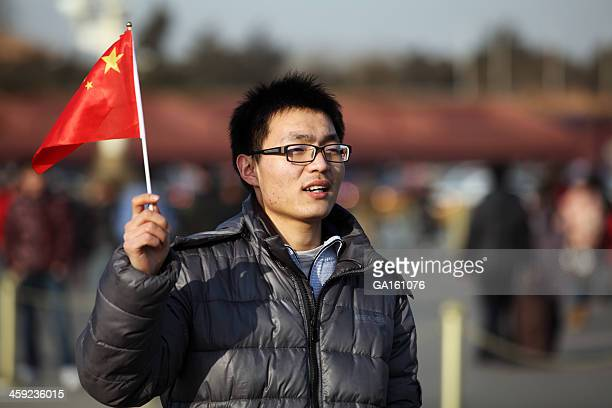 Young man with Chinese flag on Tiananmen Square in Beijing