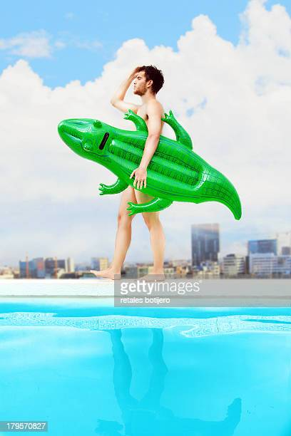Young man with crocodile inflatable in pool