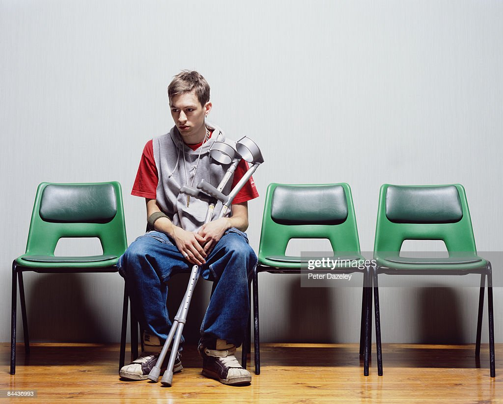 Young man with crutches sitting on hospital chairs : Stock Photo