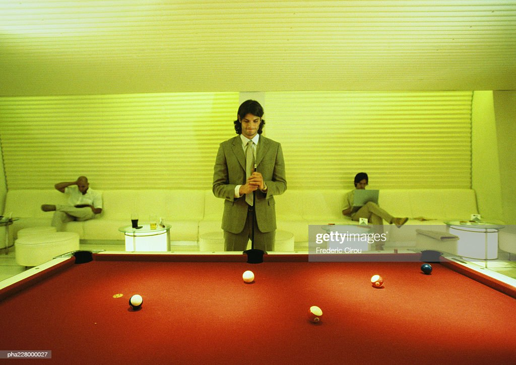 Young man with cuestick, standing at pool table, pool table in foreground, men sitting in background : Stockfoto