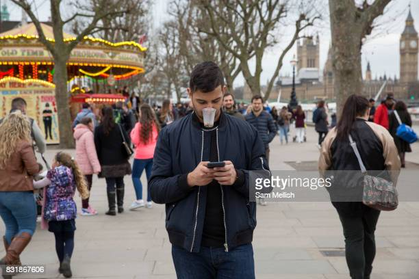A young man with cup in mouth walks along The South Bank checking his mobile phone on 19th February 2017 in London United Kingdom The South Bank is...