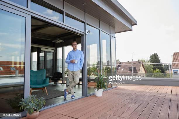 young man with cup of coffee standing at balcony door - aussicht genießen stock-fotos und bilder
