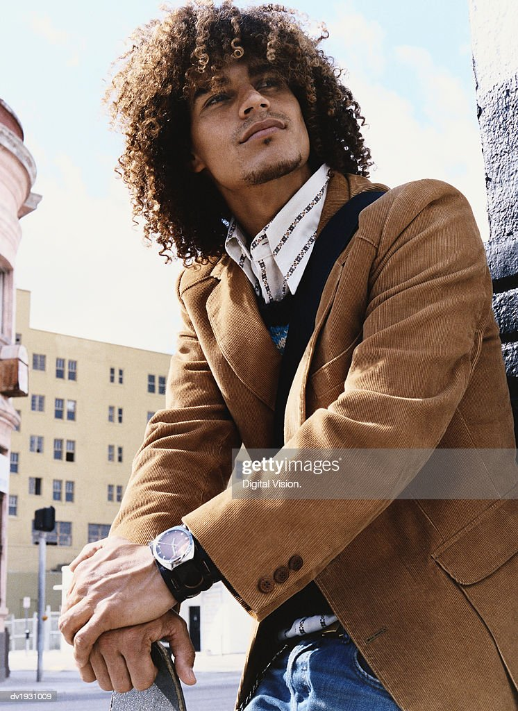 Young Man With Curly Hair Stands in an Urban Setting, Leaning on a Skateboard : Stock Photo