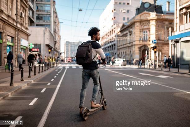 jeune homme avec la coiffure bouclée conduisant un scooter électrique de poussée autour de la ville - être en mouvement photos et images de collection