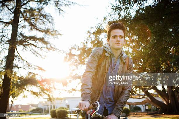 young man with cycle waiting and looking away - monrovia california stock pictures, royalty-free photos & images