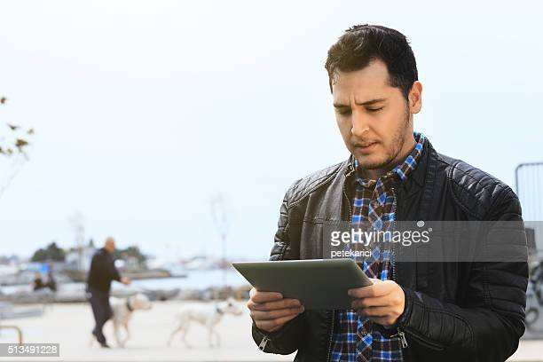 Young man with digital tablet at the park