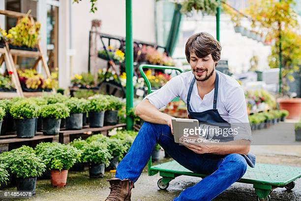 Young man with digital tablet in garden center