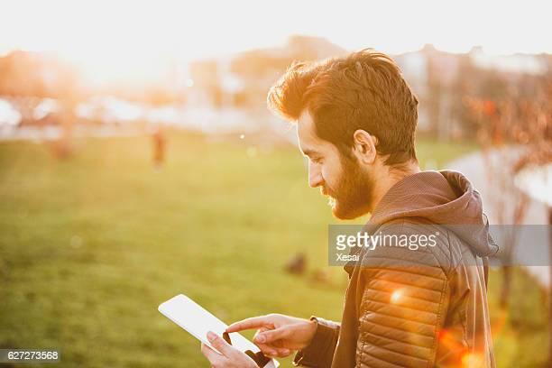 Junger Mann mit tablet PC in der Stadt