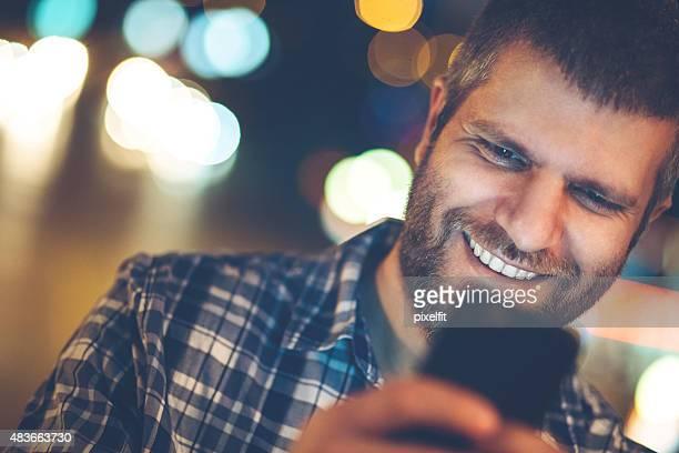 Junger Mann mit digitalen tablet im Freien bei Nacht