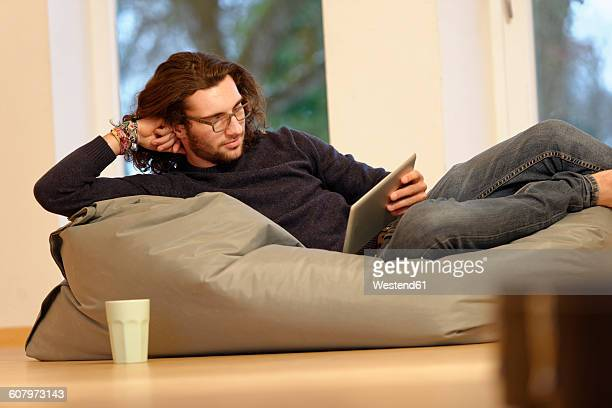 Young man with digital tablet relaxing on bean bag