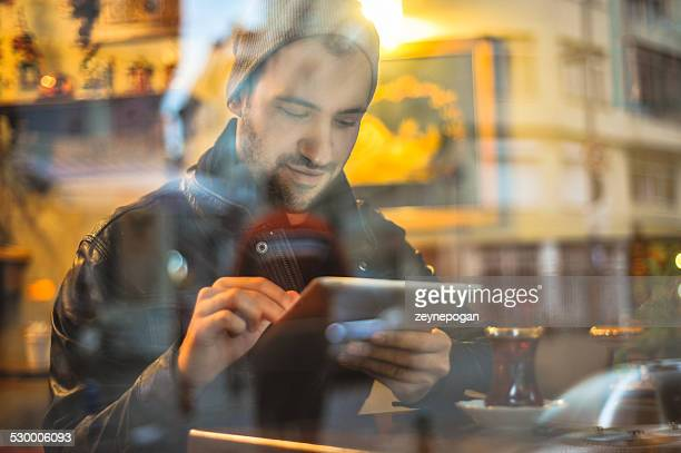 Young man with digital tablet sitting in a cafe