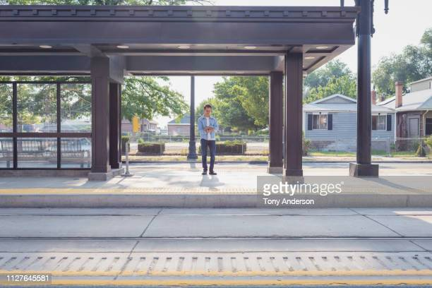 young man with digital tablet standing on commuter train platform - railroad station platform stock pictures, royalty-free photos & images