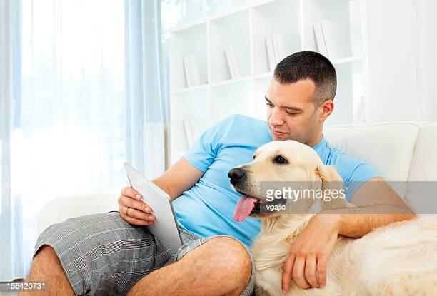 Jeune homme avec chien lisant un e-book sur tablette numérique.