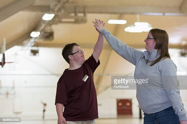 Young man with Down Syndrome doing a High-Five with student in gym
