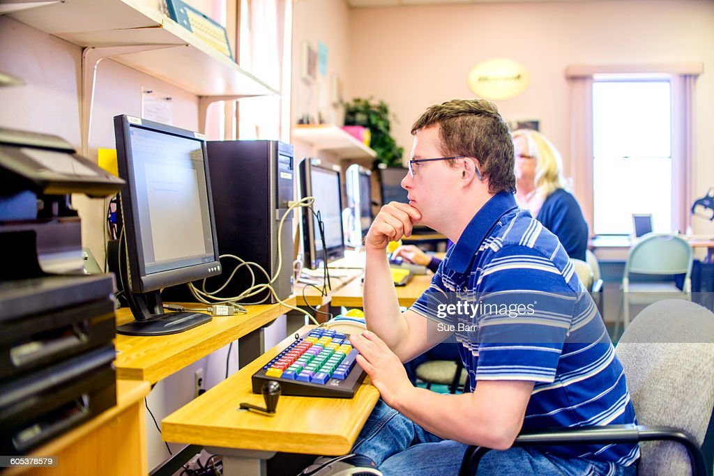 Young man with down syndrome, learning at computer : Stock Photo