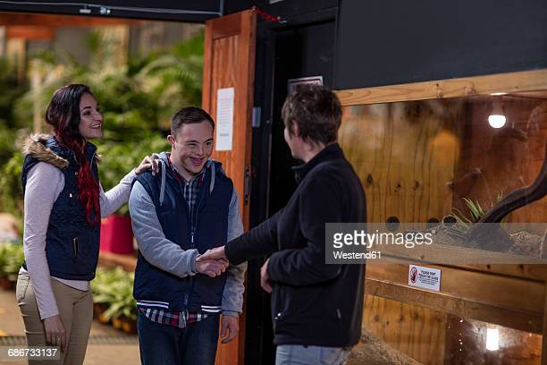 young man with down syndrome shaking hands with woman at reptile exhibition - intellectually disabled stock pictures, royalty-free photos & images
