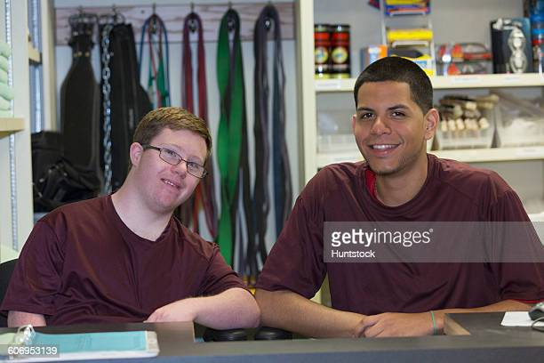 Young man with Down Syndrome working at college equipment dispensary for gym with his supervisor