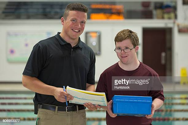 Young man with Down Syndrome working at college recording PH from swimming pool