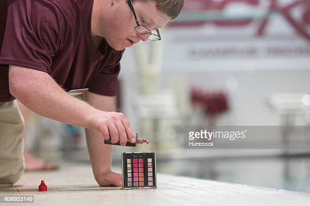 Young man with Down Syndrome working at college testing PH in swimming pool