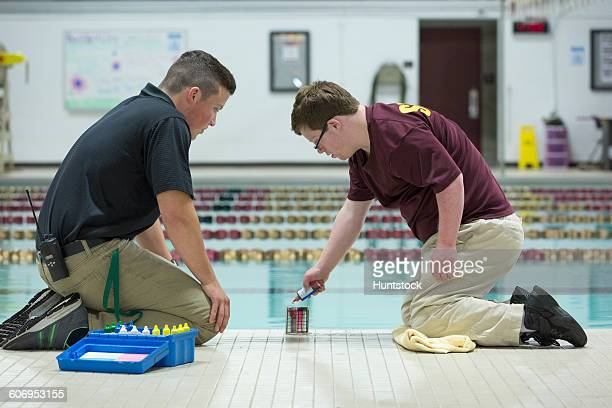 Young man with Down Syndrome working at college testing PH in swimming pool with supervisor