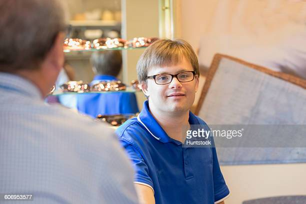 young man with down syndrome working in the glasses fitting department in a health clinic  - discapacidad intelectual fotografías e imágenes de stock