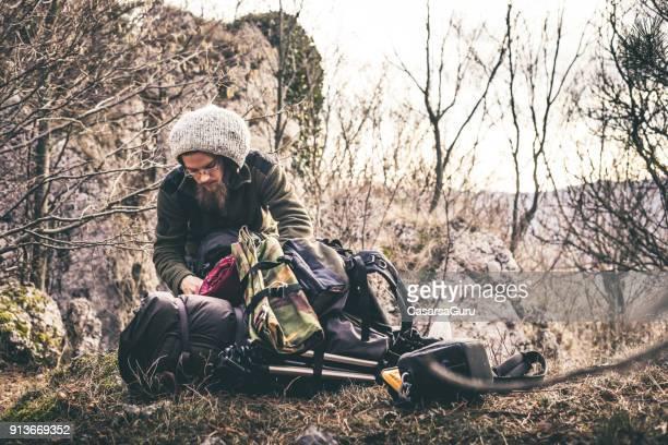 ung man med dreadlocks bläddra igenom campingutrustning i naturen - vildmark bildbanksfoton och bilder