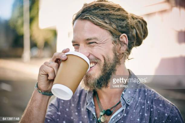 Young man with dreadlocks drinking coffee