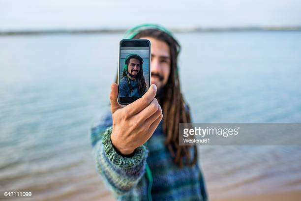 Young man with dreadlocks he take selfie with a smartphone on the beach